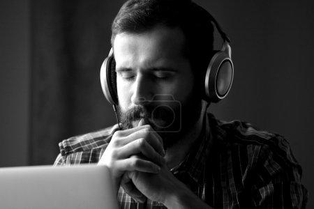 Photo pour Jeune homme barbu beau dans les écouteurs écoutant de la musique. tonification noir et blanc - image libre de droit