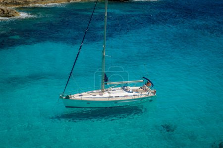 Photo pour Sailing yacht stays at beautiful water bay with clearly seen shade on the seabed. Baleares, Spain - image libre de droit