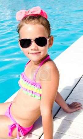 Smiling little girl sitting near swimming pool