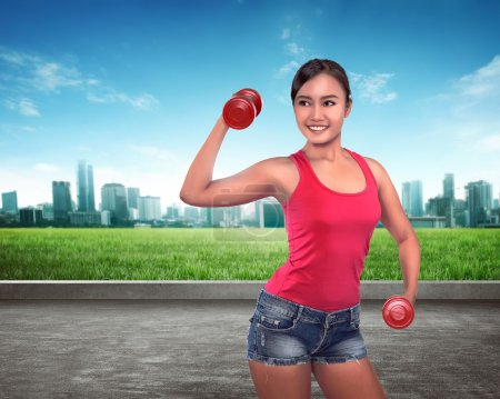 Asian woman doing exercise with dumbbells