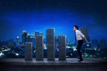 Asian businessman lifting chart block