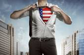Businessman tears open his shirt with american flag