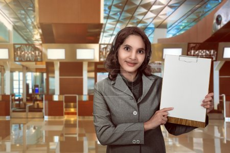 Photo for Customer service operator woman with headset smiling showing empty paperboard. You can put your design on the board - Royalty Free Image