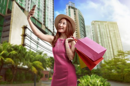 Beautiful asian woman holding shopping bags and taking selfie with cell phone