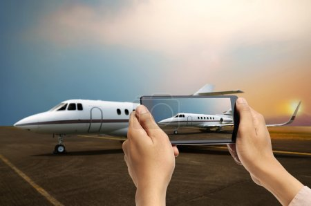 Man hand take picture of airplane using cellphone