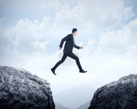 Business man jumping across hill