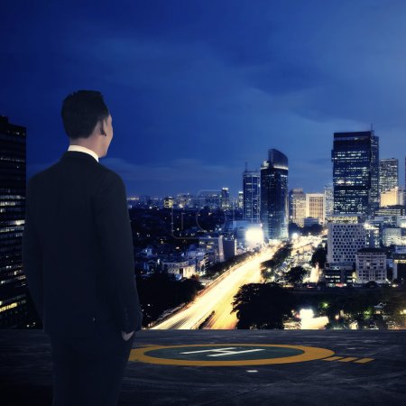 Business man standing on rooftop helipad