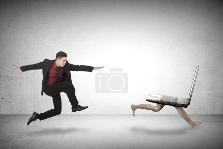 Business man chasing laptop