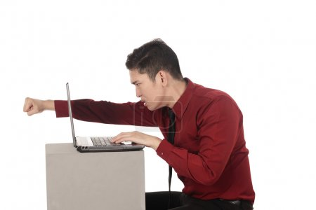Angry business man punch laptop