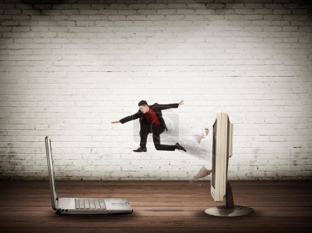 Business man jumping from desktop computer to laptop