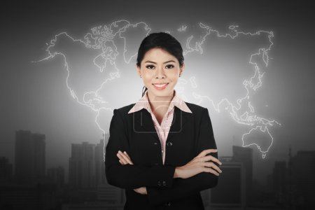 Business woman standing in front of world map