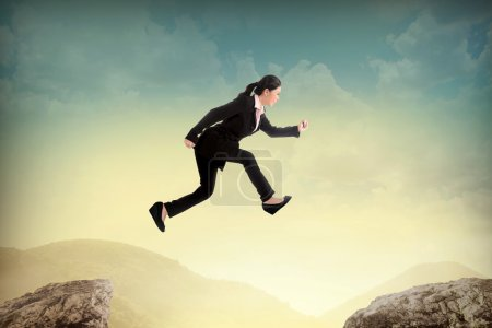 Business woman jump to another peak of mountain