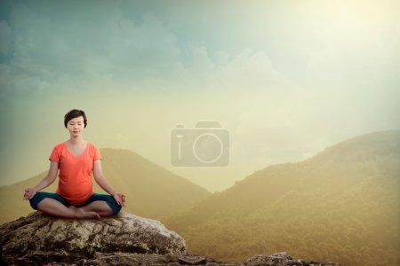 Pregnant woman doing yoga On The Mountain