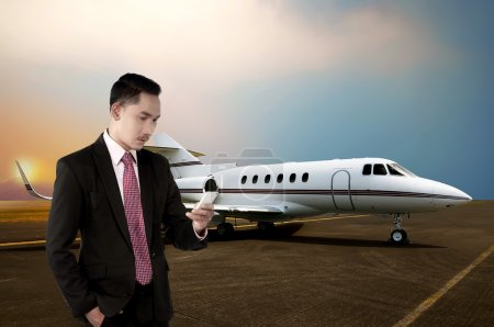 business man calling by phone near the plane
