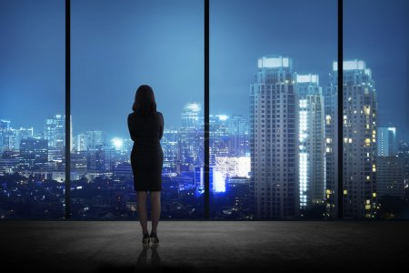 Woman standing in his office looking at the city