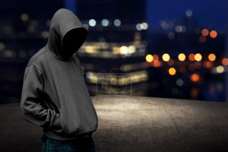 Photo pour Homme sans visage dans le capot sur le toit avec arrière-plan de la ville la nuit - image libre de droit