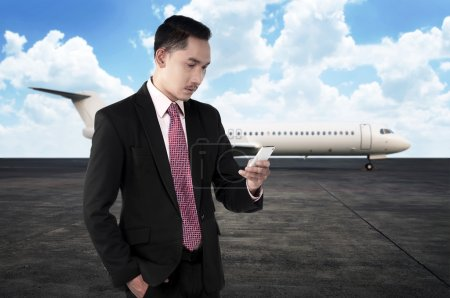 Business man calling by phone when walking to the plane