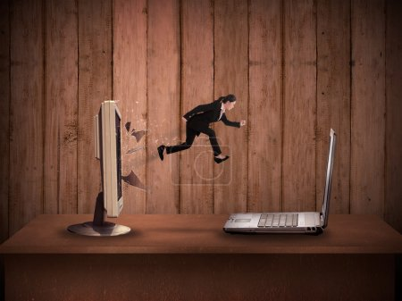 Business woman jumping from desktop computer to laptop