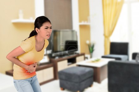 Young casual woman is having stomach ache