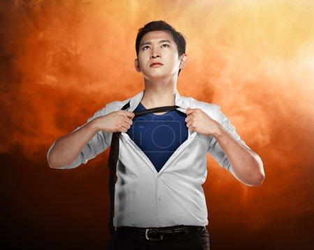 Asian businessman showing a superhero suit