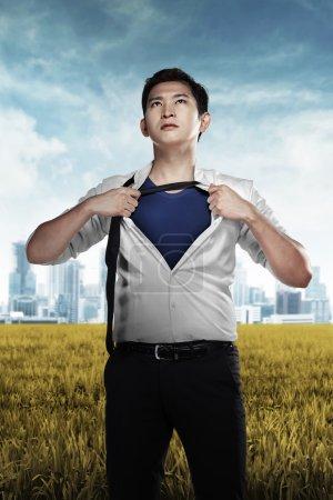 Foto de Asiático hombre de negocios mostrando un traje de superhéroe debajo de su traje - Imagen libre de derechos