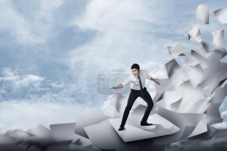 businessman surfing on the wave of papers