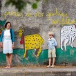Young mother and son walking outdoors in village O...