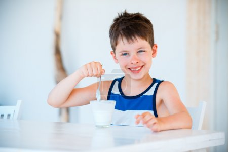 Smiling little boy eating delicious yogurt