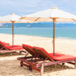 Chairs with umbrella at the empty sea beach. Beach...