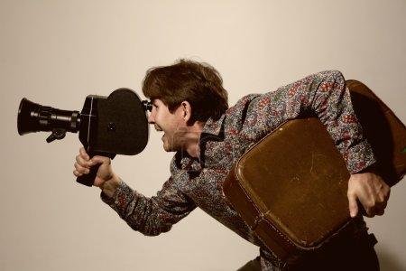 Photo pour Portrait d'un caméraman avec vieille caméra. heureux voyageurs avec une valise sur le tournage vidéo - image libre de droit