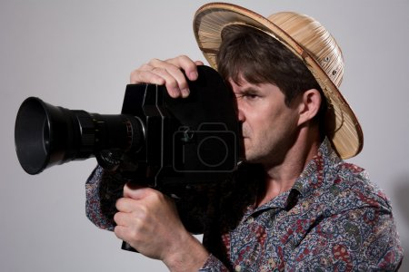 A man in a straw hat with an old movie camera on a gray backgrou