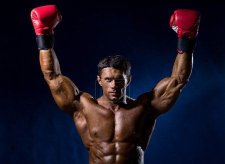 Strong muscular boxer in red boxing gloves raised his hands abov