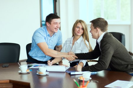Smiling man at a business meeting shaking hands with each other