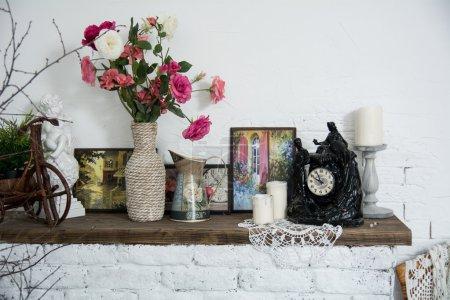 Photo pour Intérieur vases design avec des fleurs et des bougies horloge cheminée en brique. Image d'intérieur vintage pour une carte - image libre de droit
