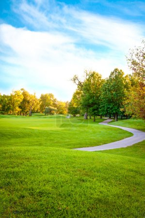 Photo for Bright green golf course sorrounded by beautiful trees - Royalty Free Image