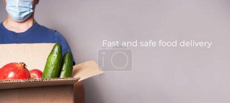 Photo pour Un messager blanc portant un masque transporte une boîte en carton d'épicerie, une livraison rapide et sûre des aliments. Bannière de haute qualité - image libre de droit