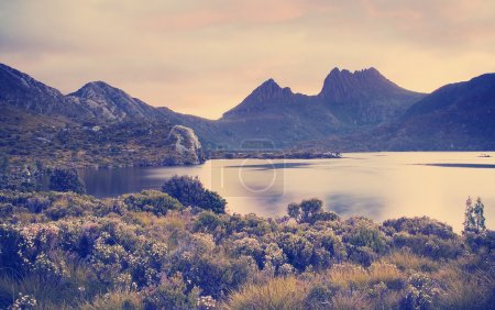 The iconic image of Tasmania, Cradle Mountain sits...