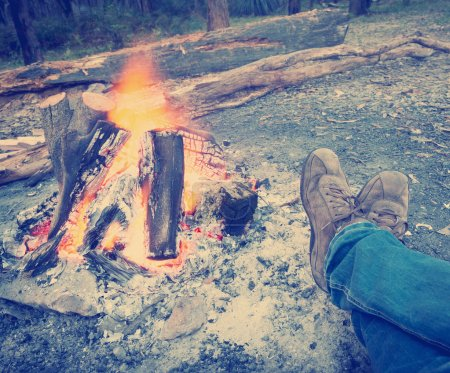 Foto de Person warms their feet next to a campfire at dusk camping in the woods with Instagram style filter - Imagen libre de derechos