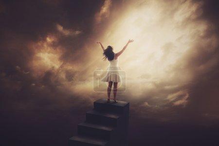 Photo pour Une femme monte au sommet d'un grand escalier pour adorer . - image libre de droit