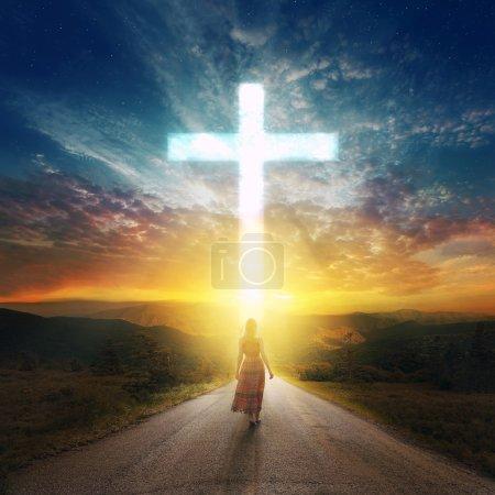 Photo pour Une femme descend une route vers une belle croix rougeoyante . - image libre de droit
