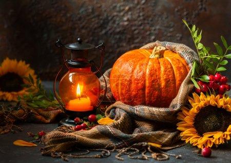 Photo pour Nature morte d'automne avec citrouille, tournesols et bougie allumée - image libre de droit