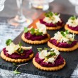 Festive appetizer: crackers with beet pesto and ch...