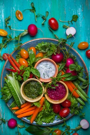 Photo for Veggie crudite platter with three different dips on wooden blue table - Royalty Free Image