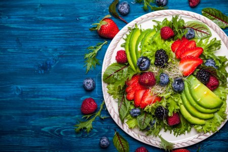 Photo for Mixed salad leaves with berries, avocado and honey-mustard dressing on white plate - Royalty Free Image