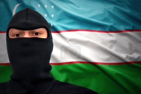 Dangerous man in a mask on a uzbek flag background...