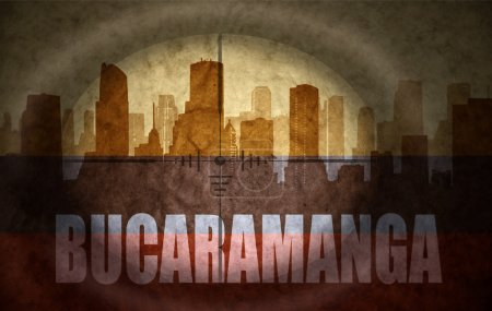 Sniper scope aimed at the abstract silhouette of the city with text Bucaramanga at the vintage colombian flag. concept
