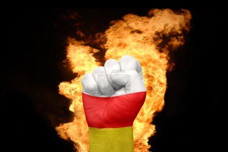 Photo pour Poing avec le drapeau national de l'Ossétie du Sud près du feu sur un fond noir - image libre de droit