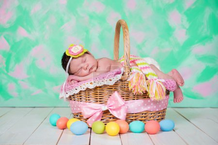 Newborn baby girl  has sweet dreams on the wicker basket. Easter Holiday