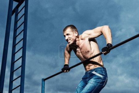 Athlete doing pull-up on horizontal bar. Mans fitness at the stadium