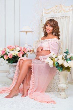Foto de Hermosa pelirroja embarazada mujer en vestido melocotón tierno se sienta cerca de floreros con rosas - Imagen libre de derechos